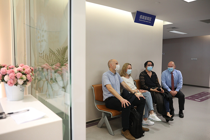 People sit in an observation area Monday in Shanghai after receiving a dose of Covid-19 vaccine. Photo: VCG