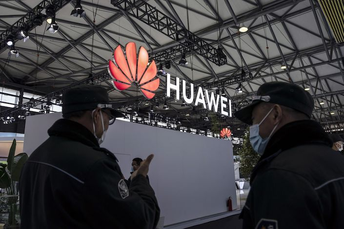 Attendees walk past the Huawei Technologies Co. logo at the MWC Shanghai exhibition in Shanghai