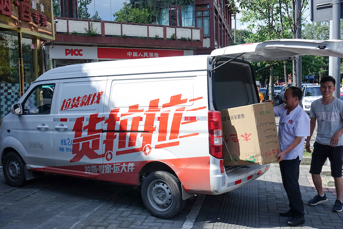 A Huolala driver unloads goods from a van.
