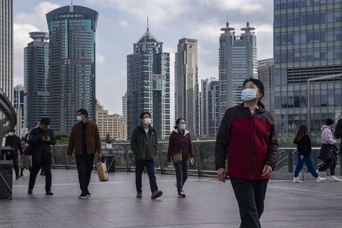 Pedestrians walk through the Lujiazui financial district in Shanghai on Dec. 1. Photo: Bloomberg