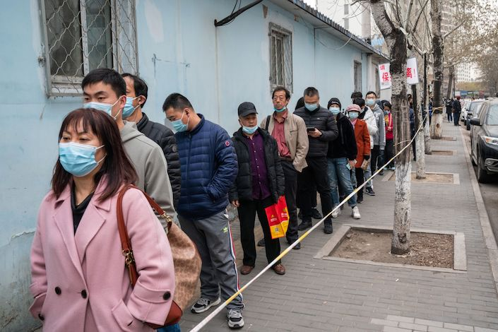 People wait in line outside a Covid-19 vaccination center in Beijing