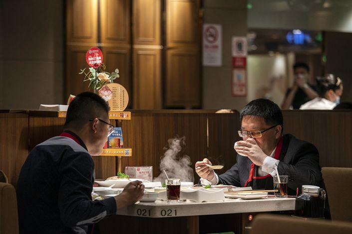Customers sit inside a Haidilao hotpot restaurant, in Shanghai, April 7. Photo: VCG