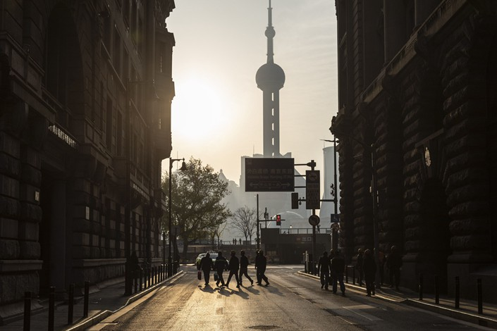 Construction workers cross a road near the Bund in Shanghai on April 10. Photo: Bloomberg