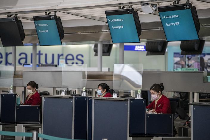 Staff at a Cathay Pacific Check in Counter in Hong Kong International Airport in Hong Kong