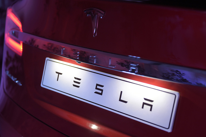 A manufacturer's name plate sits on a Tesla Model S electric vehicle during a Tesla Inc. event at the Hornsdale wind farm