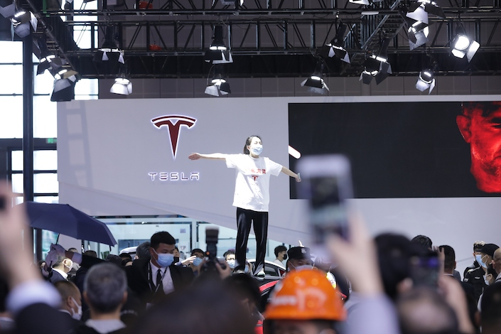 A woman climbs atop a Tesla display vehicle at the Shanghai Auto Show Monday shouting that her car's brakes failed.