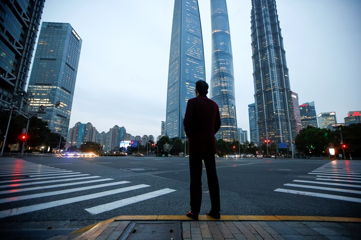 A man stands at a crossroads in Lujiazui financial district in Pudong, Shanghai, China, 5 March 2021. Photo: Reuters