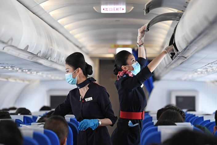 An attendant checks the overhead bins on a flight in Hefei, East China's Anhui Province, on March 2. Photo: VCG