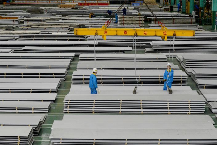 Workers move stainless steel sheets in Jingjiang, East China's Jiangsu province, on April 15. Photo: VCG
