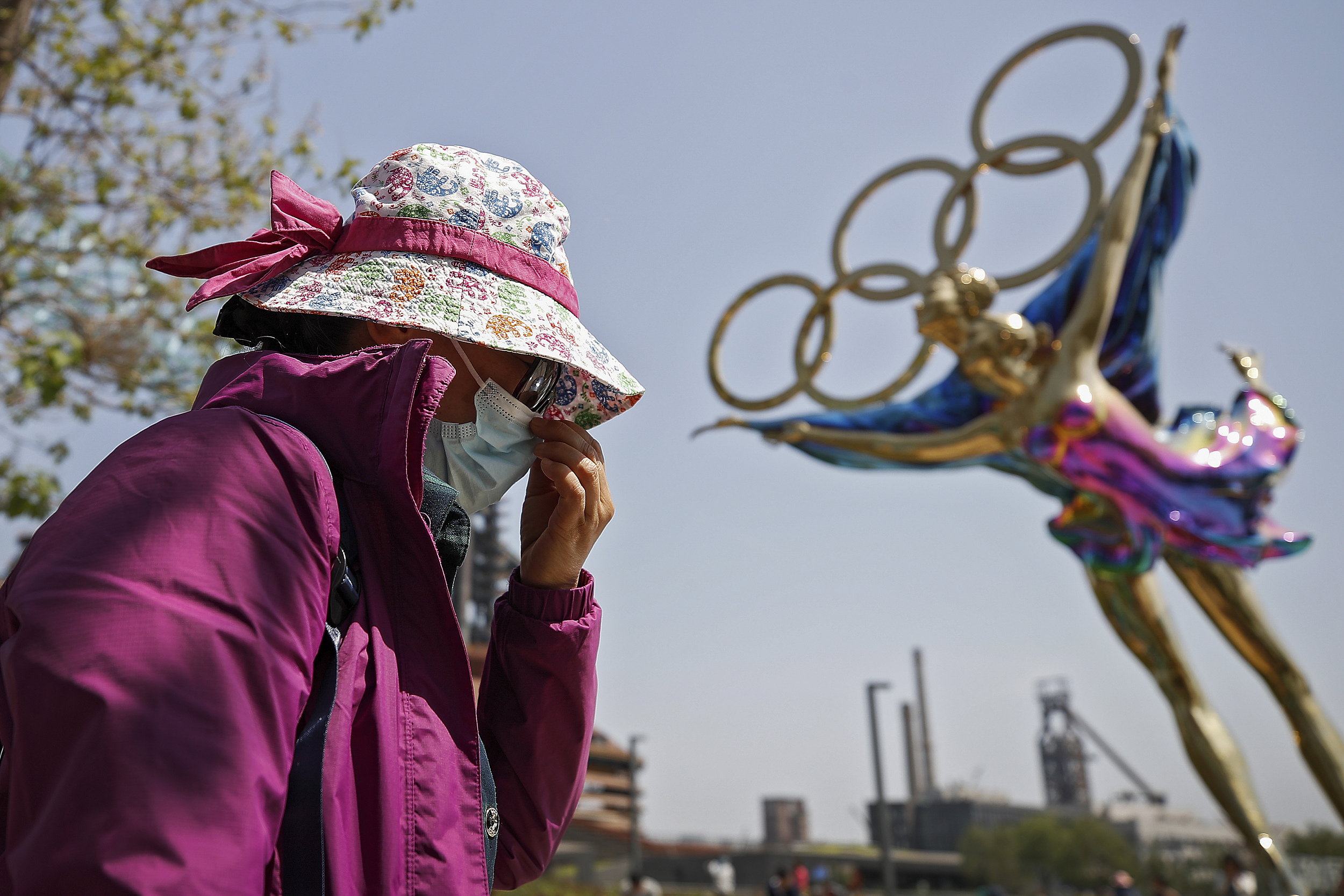 A woman adjusts her face mask as she walks by a statue featuring the Winter Olympics figure skating on display at the Shougang Park in Beijing, Sunday, May 2. Photo: VCG