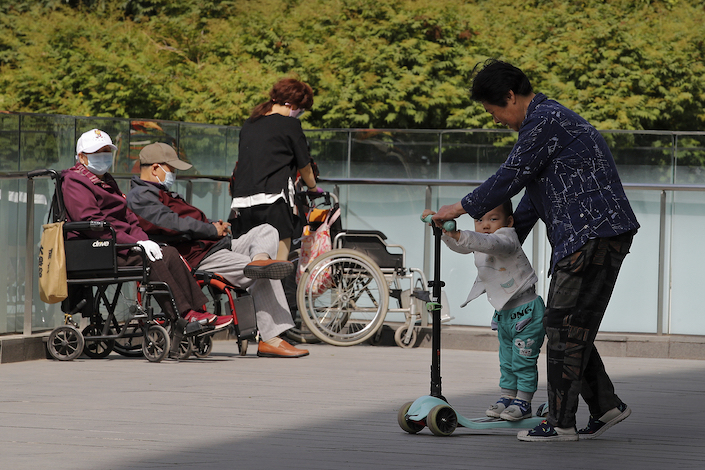 A woman plays with a child near elderly people on wheelchairs sunbathing on a compound of a commercial office building in Beijing