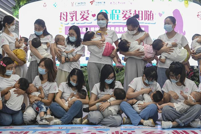 A group of 20 mothers hold their babies during a