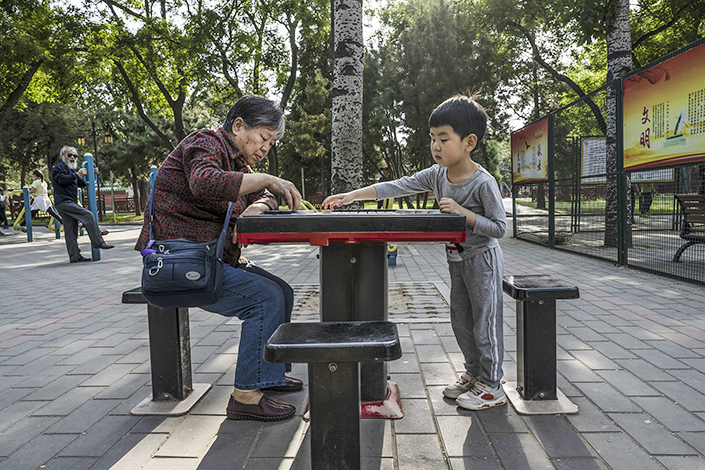 A kid plays Chinese chess with his grandma in a Beijing park on May 12. Photo: VCG