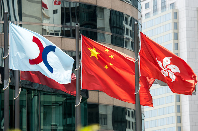 The Hong Kong Exchanges and Clearing Limited (HKEX) flag (L) flies outside the HKEX building in Central.