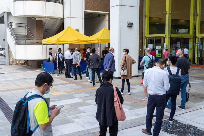 People stand in line outside a community vaccination center administering the BioNTech Covid-19 vaccine imported by Fosun Pharma in Hong Kong
