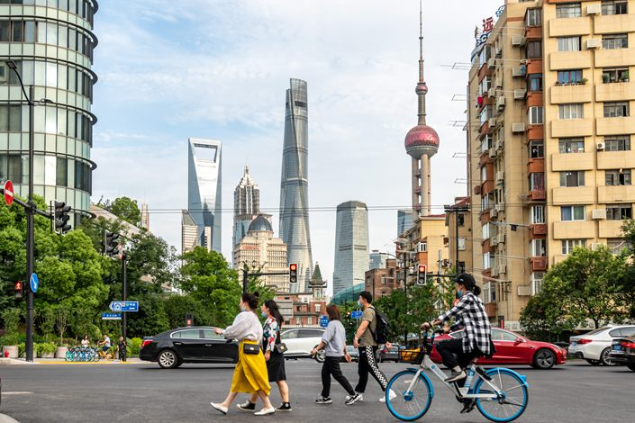 Residents travel down a street in Shanghai on Monday. Photo: VCG