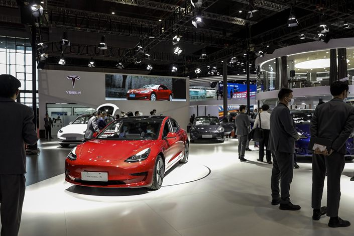 Visitors walk past Chinese-made Tesla electric vehicles at the company's booth at an auto show in Shanghai on April 19. Photo: Bloomberg
