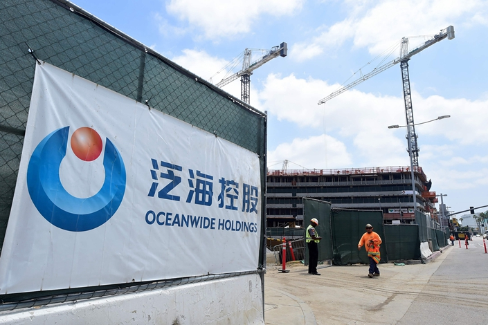 A banner of China's Oceanwide Real Estate Group is displayed at the construction site of a property. y