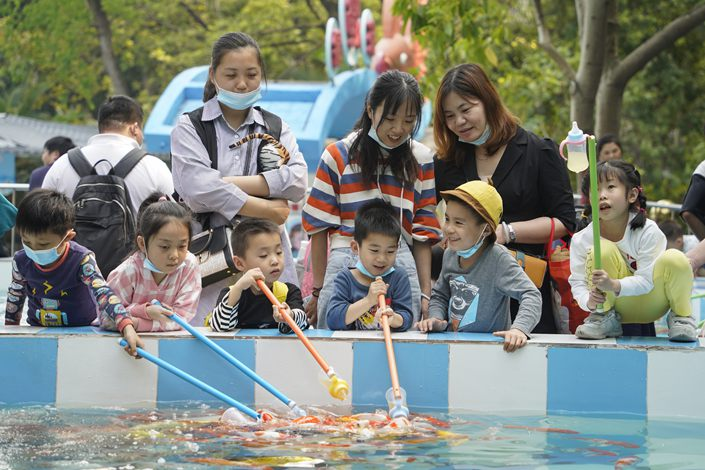 Children feed the fish with their parents in Guangzhou on April 10. Photo: VCG