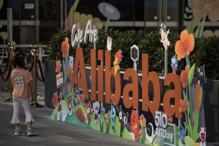 A girl stands in front of a sign at the Alibaba Group Holding Ltd. headquarters in Hangzhou