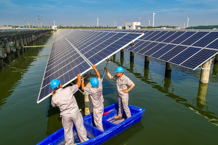 Workers at a solar power station check equipment in Nantong, Jiangsu province. Photo: VCG