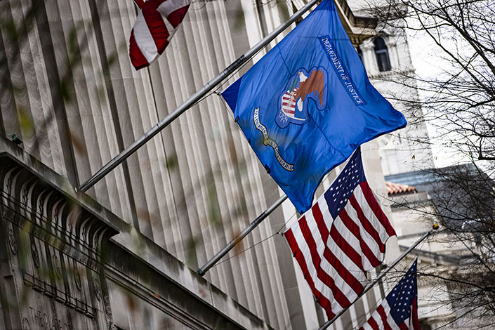 American and U.S. Department of Justice (DOJ) flags fly outside DOJ headquarters in Washington