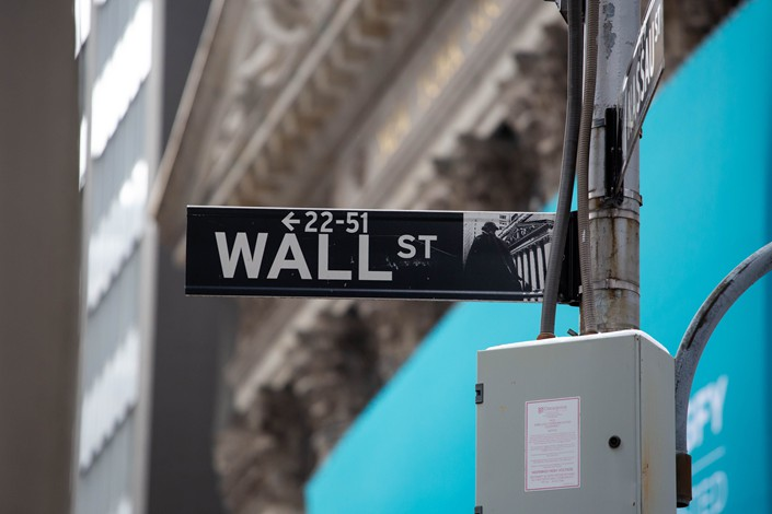 A Wall Street street sign is displayed in front of the New York Stock Exchange on Feb. 11. Photo: Bloomberg