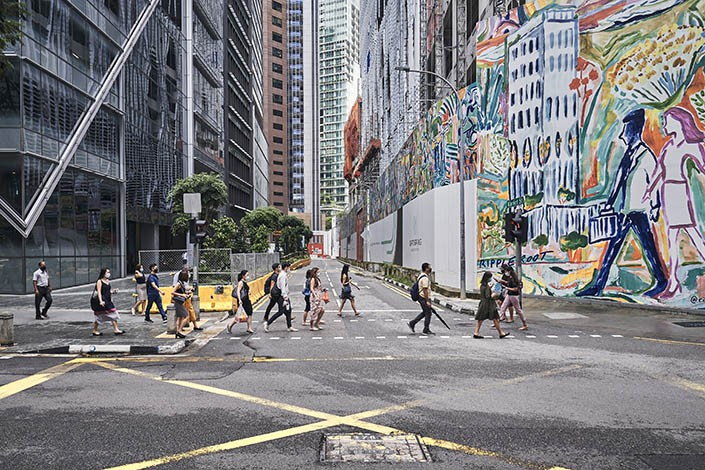 Pedestrians walk down a street in Singapore on Oct. 1. Photo: VCG