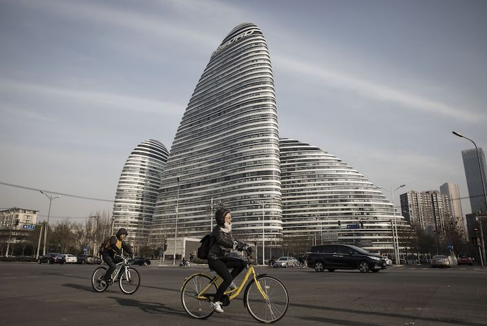 Commuters ride bicycles past commercial buildings at the Soho China Ltd. Wangjing Soho project in Beijing