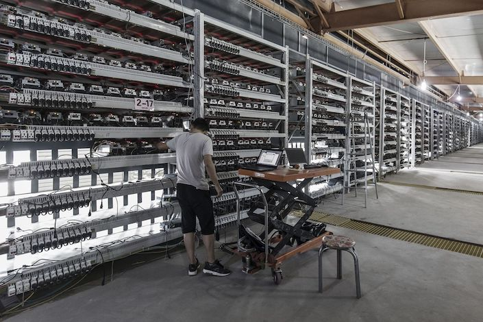 A technician inspects bitcoin mining machines at a mining facility in Ordos