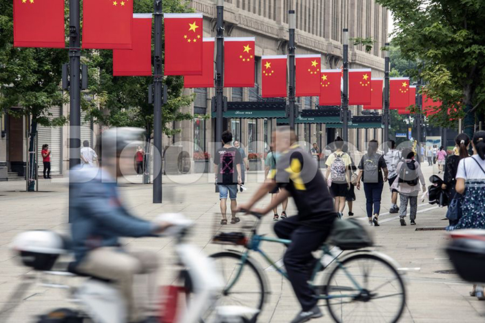 Pedestrians walk past Chinese flags hanging from lamp posts in Shanghai on Thursday. Photo: Bloomberg
