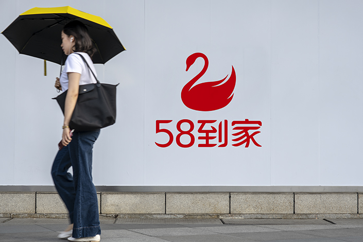 A woman passes by a wall with a 58 Daojia logo on a street. Photo: IC Photo