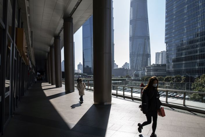 Pedestrians wearing protective masks walk through Pudong's Lujiazui Financial District in Shanghai