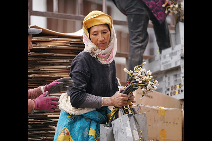 On May 2, a Tibetan woman in Sichuan province's Heishui county carries components of cryptocurrency mining machines that were sent from the Xinjiang Uyghur autonomous region. Such machines are now being deactivated following China's recent ban on cryptocurrency mining. Photo: Ding Gang/Caixin