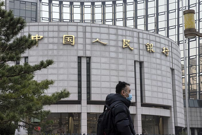 A pedestrian walks past the headquarters of the People's Bank of China in Beijing on March 4. Photo: Bloomberg
