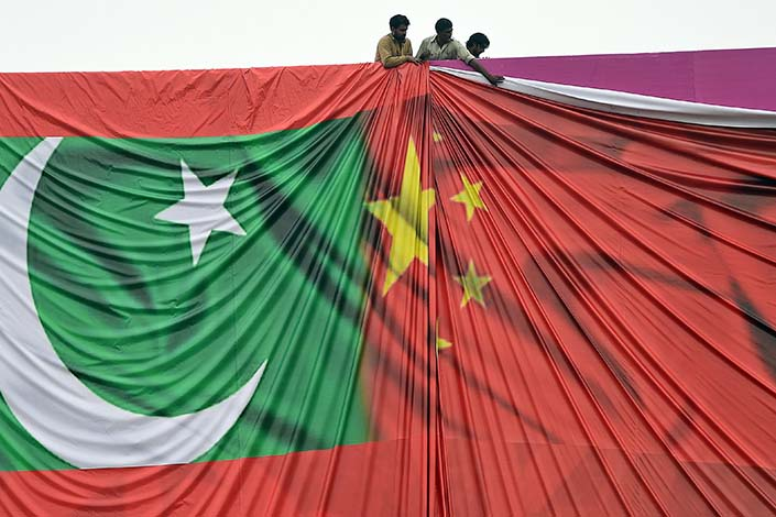 Pakistani laborers prepare a welcome billboard featuring the Chinese and Pakistani national flags ahead of the forthcoming visit by Chinese President Xi Jinping in Islamabad in April 2015. Photo: Bloomberg