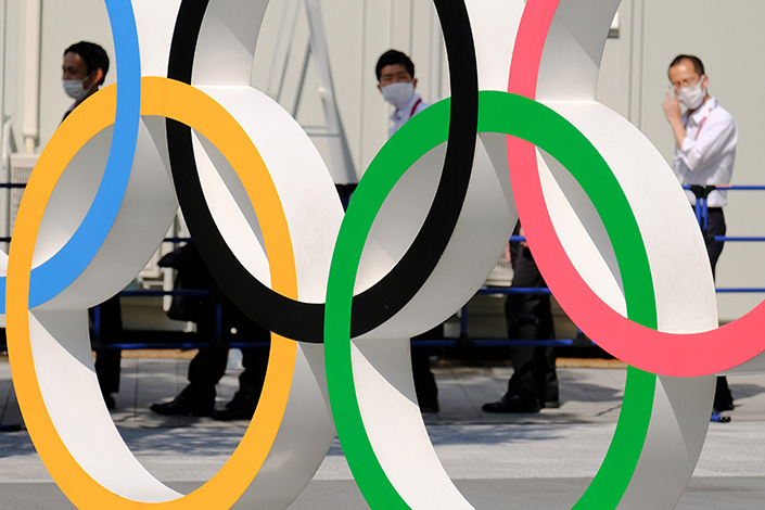 People in face masks walk past the Olympic Rings near the National Stadium in Tokyo on Sunday. Photo: VCG
