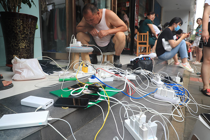Residents charge electric devices at stores on Thursday in Zhengzhou, where the store owners are providing free chargers. Photo: VCG