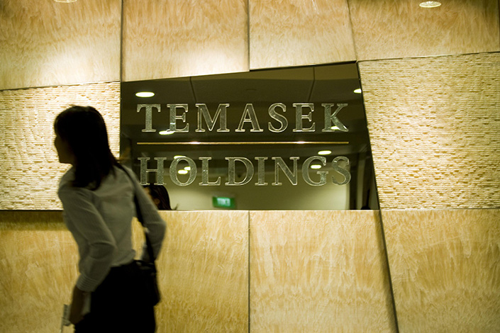 A passenger walks past a company sign of Temasek Holdings in Singapore on Feb. 6, 2009. Photo: IC Photo.