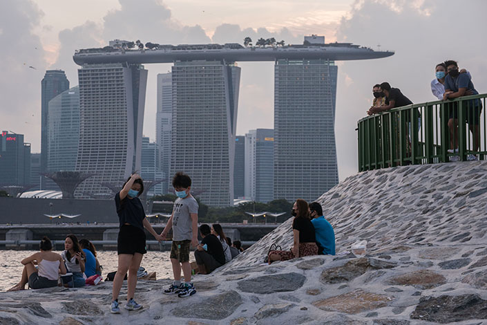 People wearing masks relax on a breakwater with the Marina Bay Sands in Singapore on June 6. Photo: IC Photo.