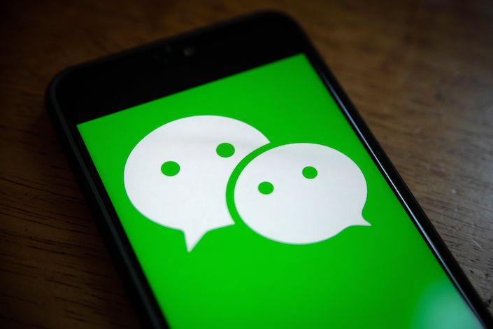 The logo for Tencent Holdings Ltd.'s WeChat app is arranged for a photograph on a smartphone in Hong Kong