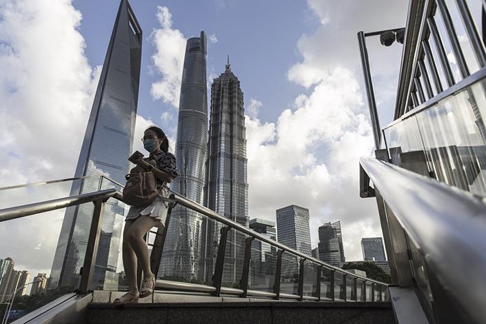 A pedestrian walks along a footbridge in Shanghai's Lujiazui financial district Tuesday. Photo: Bloomberg