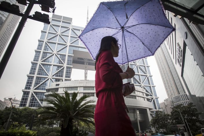 A pedestrian carrying an umbrella walks past the Shanghai Stock Exchange building in Shanghai