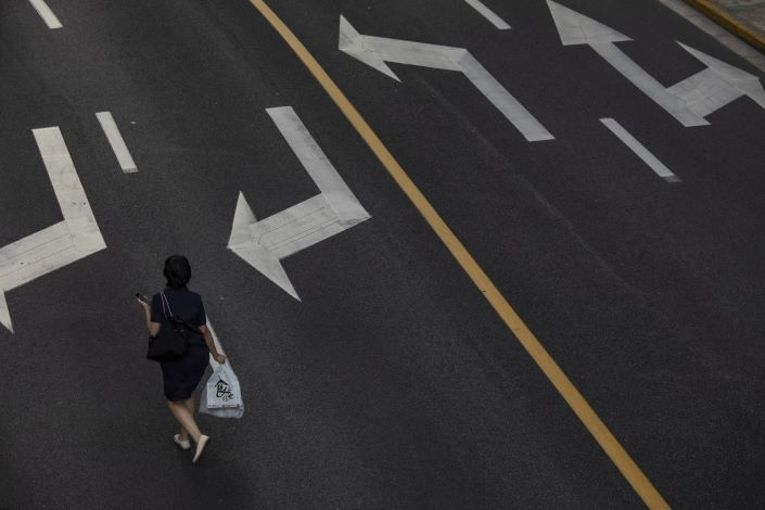 A pedestrian walks along a road in the Lujiazui business district in Shanghai on Tuesday.  Photo: Bloomberg