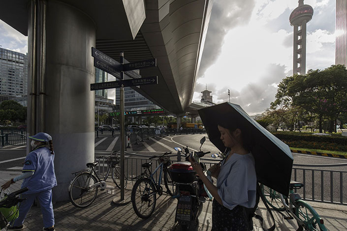 A pedestrian uses a smartphone in Shanghai's Lujiazui business district on July 20. Photo: Bloomberg