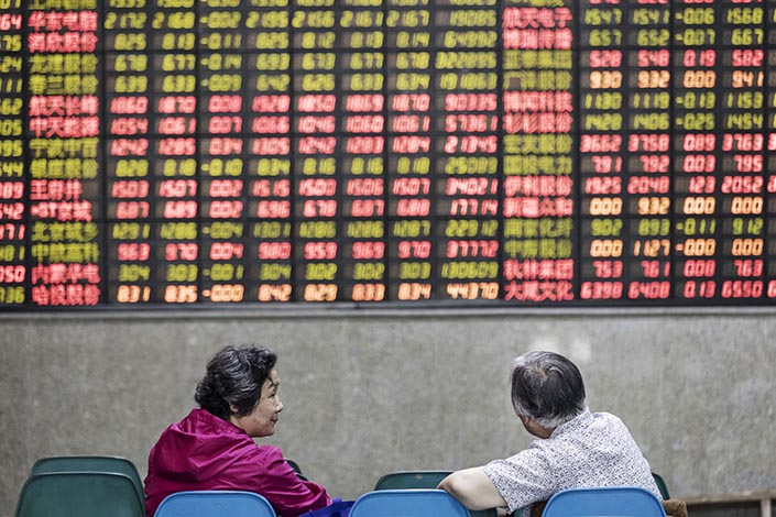 Investors sit in front of an electronic stock board at a securities brokerage in Shanghai