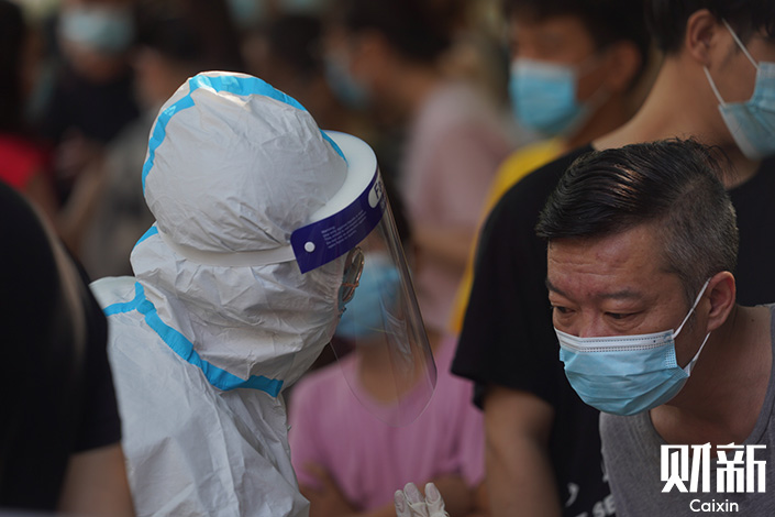 A medical worker communicates with a citizen in Zhengzhou, Central China's Henan province, on Saturday. Photo: Chen Liang/Caixin