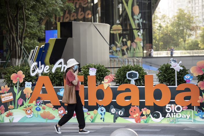 A person walks past a sign at the Alibaba Group Holding Ltd. headquarters in Hangzhou