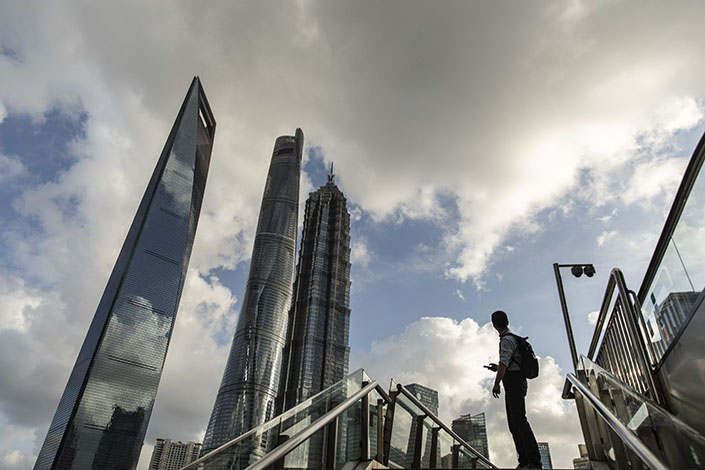 A pedestrian pauses on a footbridge in the Lujiazui business district in Shanghai on July 20. Photo: Bloomberg