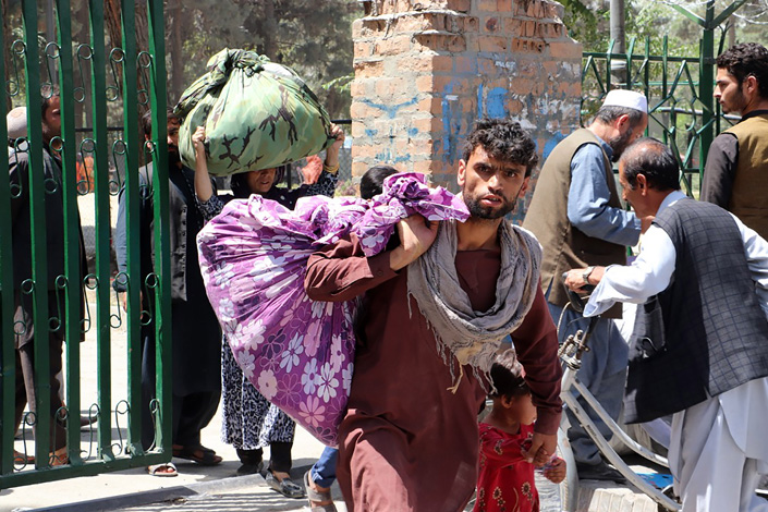 People carry their belongings after the Taliban entered Kabul, Afghanistan, on Sunday. Photo: VCG